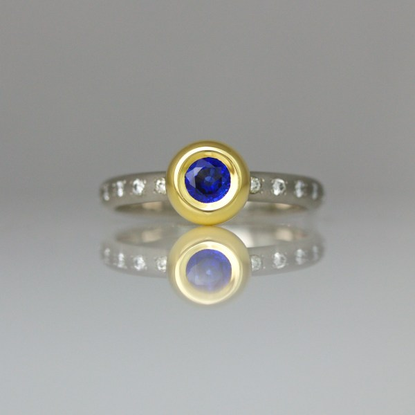 Sapphire rub-over set in yellow gold on a diamond set platinum ring
