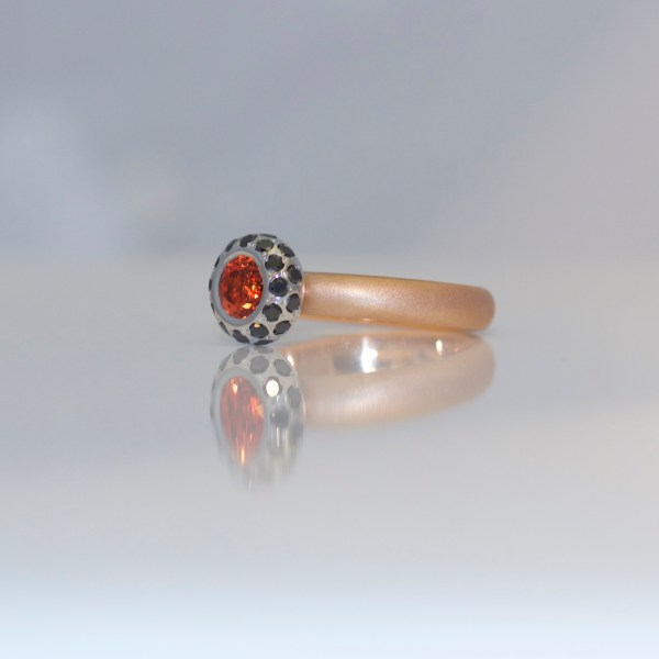 Orange sapphire framed with black diamonds ring