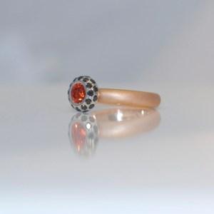 Orange sapphire framed with black diamonds ring