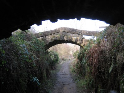 Ramshackle stone bridge over a path, shot from the mouth-like gap of the bigger bridge running under the road by the Coppice Pond