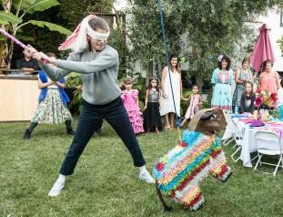 Photo of girl hitting Fiesta piñata
