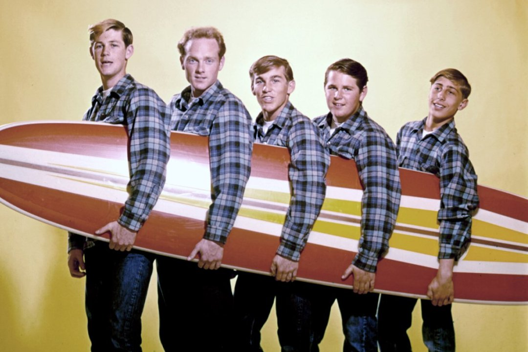 "Picture of LOS ANGELES - AUGUST 1962: Rock and roll band ""The Beach Boys"" pose for a portrait with a surfboard in August 1962 in Los Angeles, California. (L-R) Brian Wilson, Mike Love, Dennis Wilson, Carl Wilson, David Marks. This image was used on the cover of 'Surfin' USA'. (Photo by Michael Ochs Archives/Getty Images)"