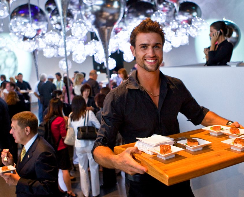 Bouley Catering - A male server dressed in black with a broad smile is walking up the stairs holding a big wooden tray of canapes.