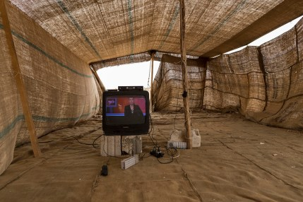 A telly in a make-shift tent. The families in this encampment have settle close to a food packaging plant where many of the adults are working illegally for low pay and the provision of water and electricity. The children, meanwhile, have little to occupy their time. None are in education and the TV offers them a little respite and distraction.