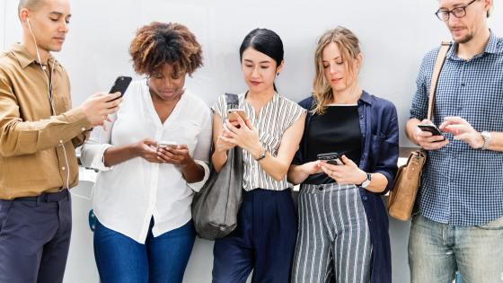 5 adults glancing at their personal devices