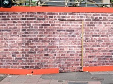 Photograph of a brick wall hiding construction work on a supermarket.