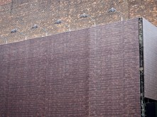 This is a mesh stretched over scaffolding, onto which is printed a brick wall. It masks a poor quality real brick wall and carries large advertising hoardings.