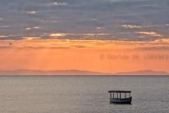 Le acque scure e calme del lago contrastano con il colore del cielo mentre alcuni raggi del sole che tramonta riescono a forare lo spesso strato di nubi e dando emozioni al fortunato viaggiatore seduto sulla riva.