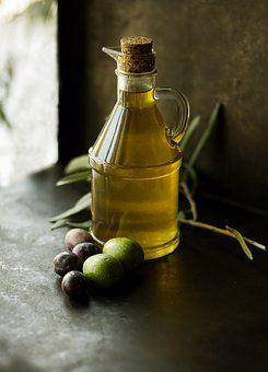 Botella de aceite junto a aceitunas