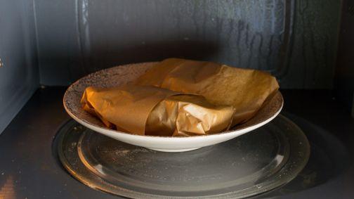 Patatas envueltas en papel de cocina dentro del microondas