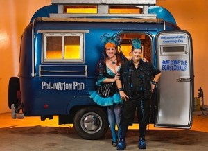 Annie Sprinkle and Beth Stephens standing in front of a van