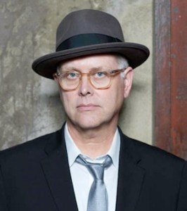 Photo of Eddie Muller wearing glasses and a hat, very noir