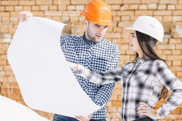 architects in front of brick wall 23 2147813096 - DIY vs. Hired: Pros and Cons of Each Construction Approach