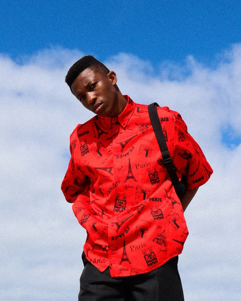 DJ and creative Shayne Tino stands against a blue sky in a bright red button up shirt. It has an Eiffel Tower print.