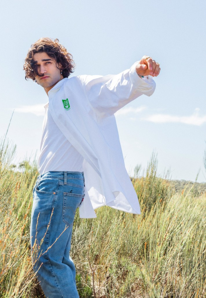 Actor Josh Heuston stands in a field wearing a white Balenciaga button up shirt with a prominent lime green logo on the left pocket over a white t-shirt and Tommy Jeans.