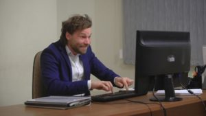 Active businessman rejoices success. In the office, sitting at the computer