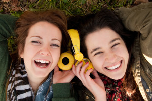 Two happy teenage girls lying on the grass sharing headphones to listen to music
