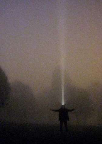 Cosmic calling - man creature emits beam of light to sky