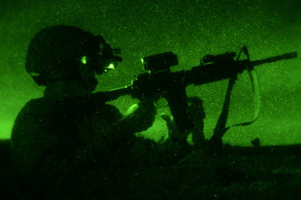 The DET, image of military operator reloading an M4 rifle at night with green background as seen through night vision goggles.