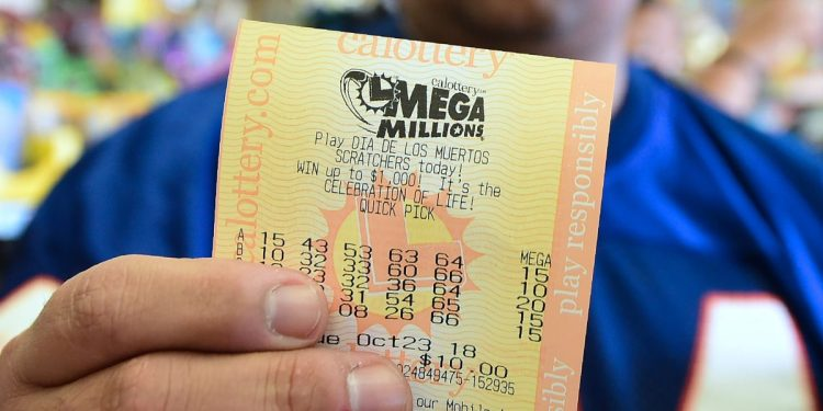 A man shows his just purchased lottery tickets from the Blue Bird Liquor store in Hawthorne, California on October 23, 2018 ahead of the drawing tonight for the Mega Millions jackpot, now reaching USD 1.6 billion. (Photo by Frederic J. BROWN / AFP) (Photo credit should read FREDERIC J. BROWN/AFP/Getty Images)