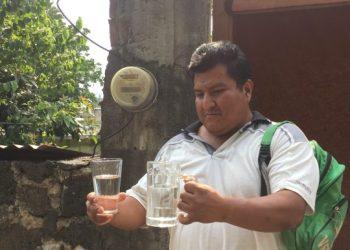 Felipe Ríos, vecino de Ocotepec, hace la comparativa entre agua pura y la contaminada con gasolina.