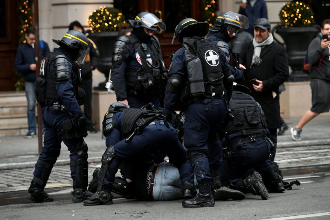 "French CRS riot police apprehend a protester during clashes at a national day of protest by the ""yellow vests"" movement in Paris, France, December 8, 2018. REUTERS/Piroschka van de Wouw"