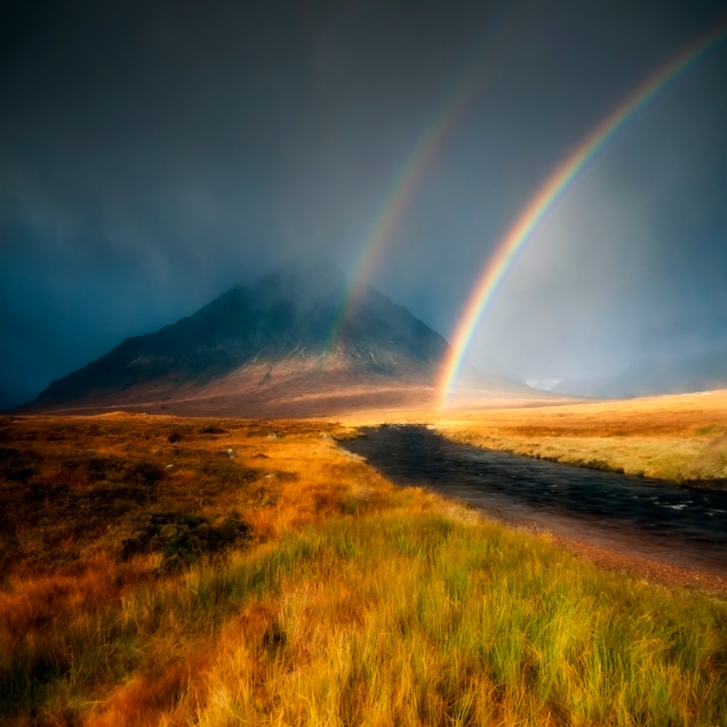 Two rainbows arc towards a mountain in the distance , the buachaille etive mor in Glencoe