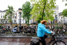 A woman cycles in the rain in Utrecht, Netherlands.