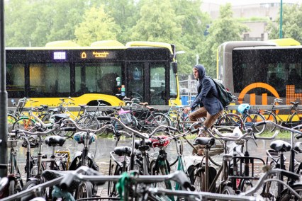 A man cycles in the rain in Utrecht, Netherlands.