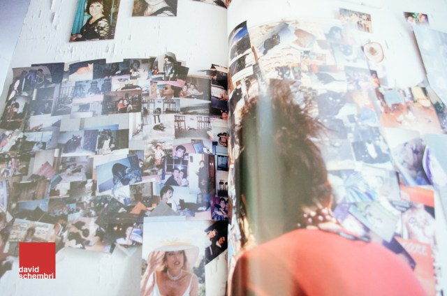 A photo of a printed photo of a woman looking at lots of photos