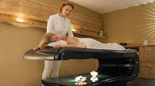 massage therapist delivering mindful medical massage therapy to a client on table