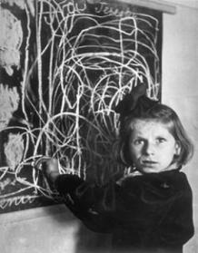 "Terezka, a disturbed child in an orphanage. The scrawl on the blackboard is her drawing of ""home"". Poland, 1948"