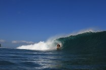 Photo of David Sills - Surfer-Saxophonist crouching on his surfboard riding a large tubular wave as it crests and crashes behind him