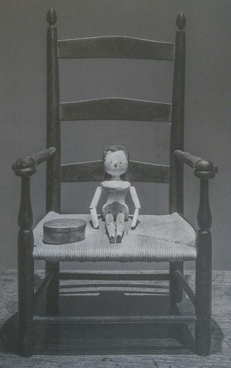 Image of wooden doll on a chair
