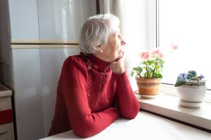 Old lonely woman sitting near the window at home. Concept of quarantine, coronavirus