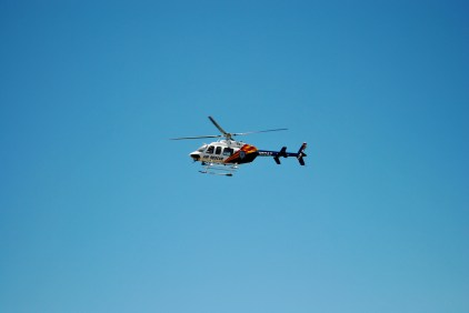 A rescue helecopter searching the trails.