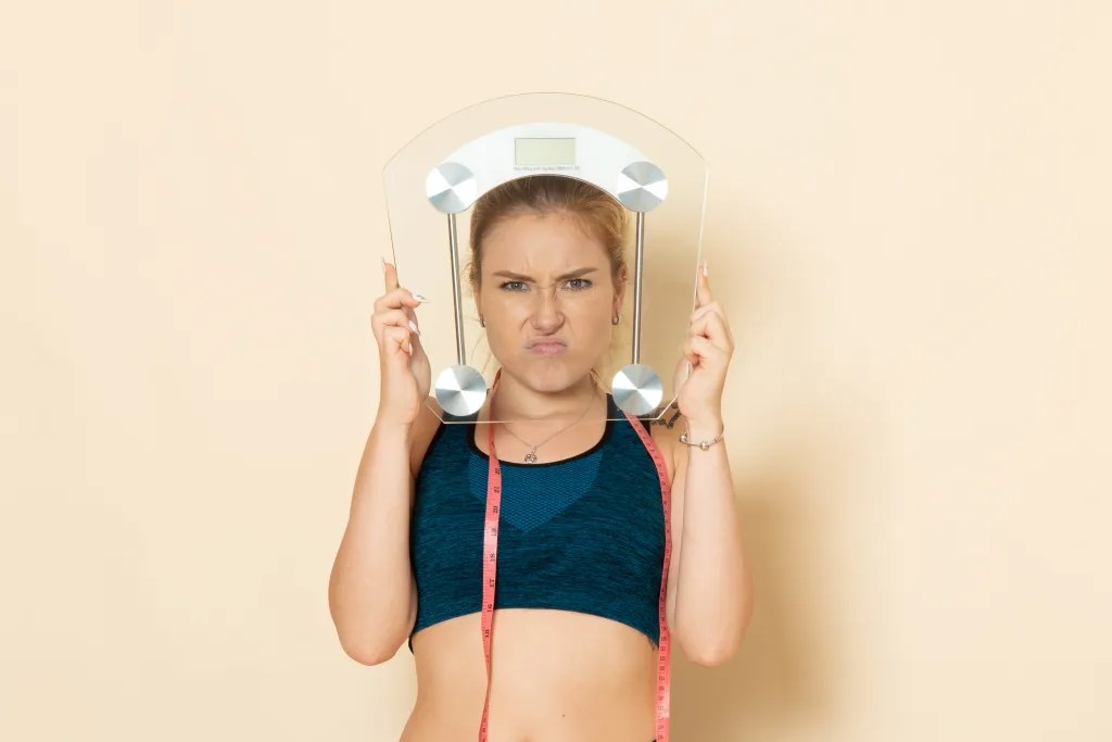 Angry young lady holding bathroom scales up.
