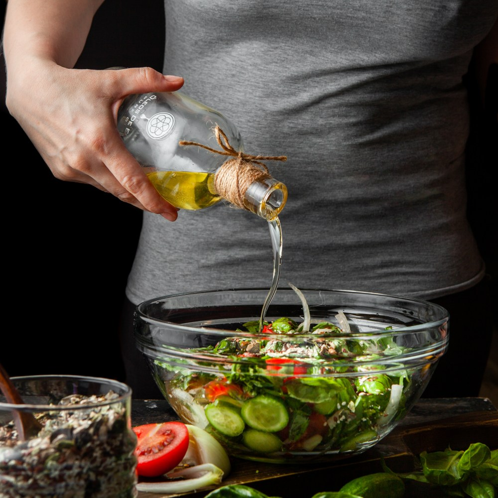 woman pouring olive oil into salad