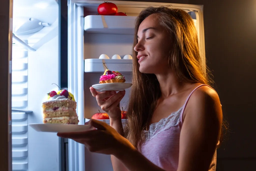 Woman raiding the refrigerator for sweets.