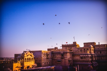 Where am I? Dance the pigeons around my head like on any public place in Paris. The sun rising over the desert is starting to reveal the golden buildings arising from the sand. Is this sun the same as before? Is there only one sun lighting all the places in the world? Certainly not. Jaisalmer, India, 2014