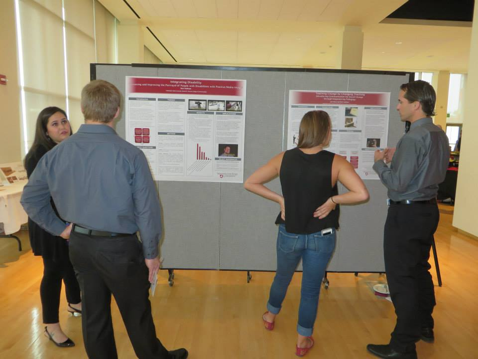Photo of Davi and Joe Hewa presenting posters to an audience.