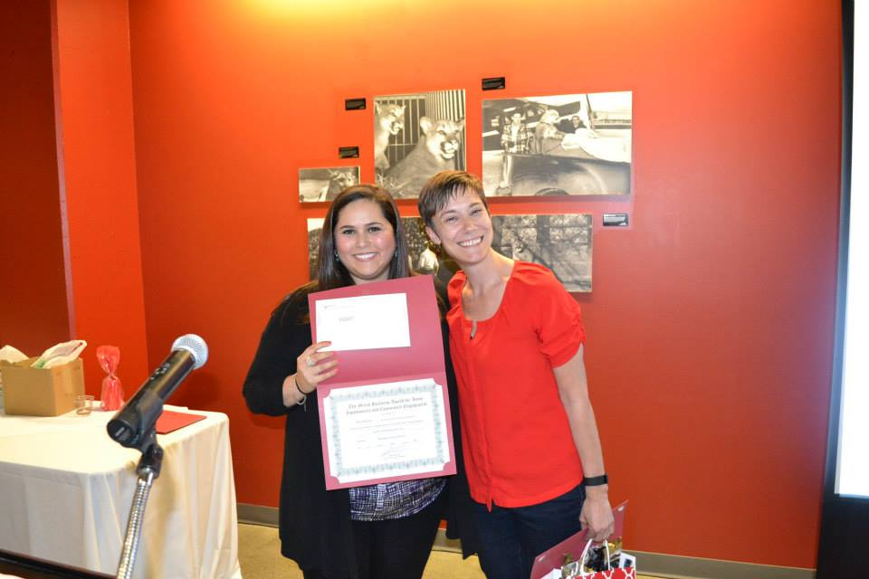 Photo of Davi with former WSU faculty member Myiah Hutchens. They are smiling at the camera and Davi is holding up a paper certificate.