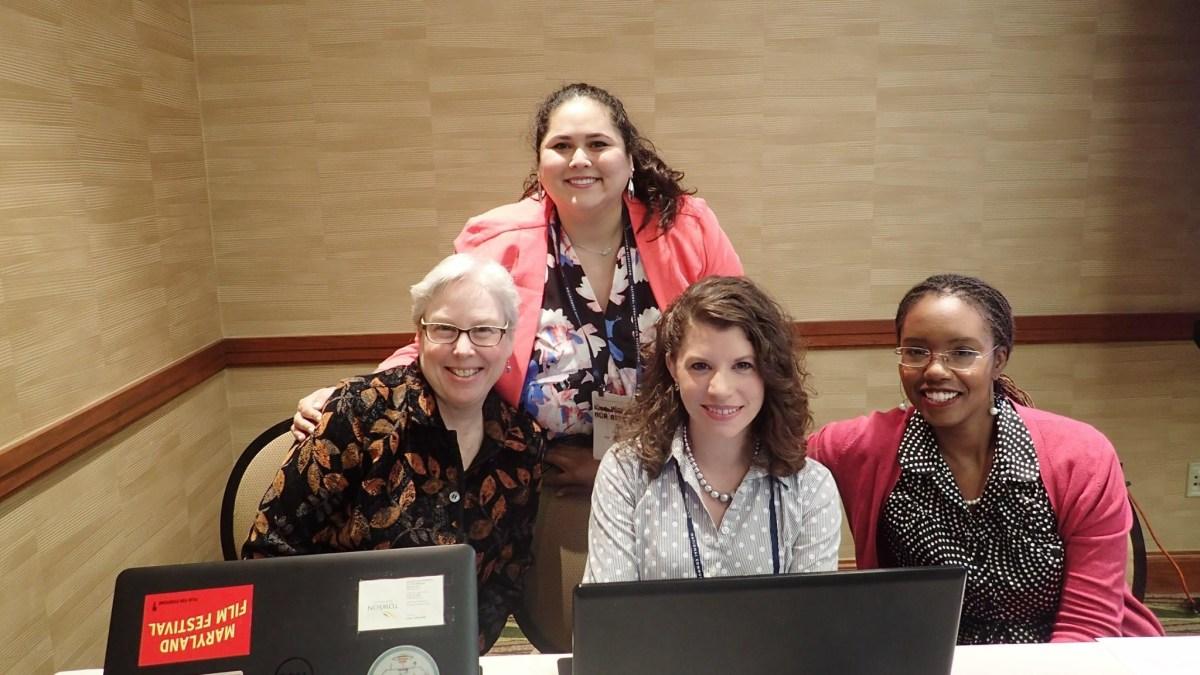 Photo of Davi Smiling and standing behind three women.