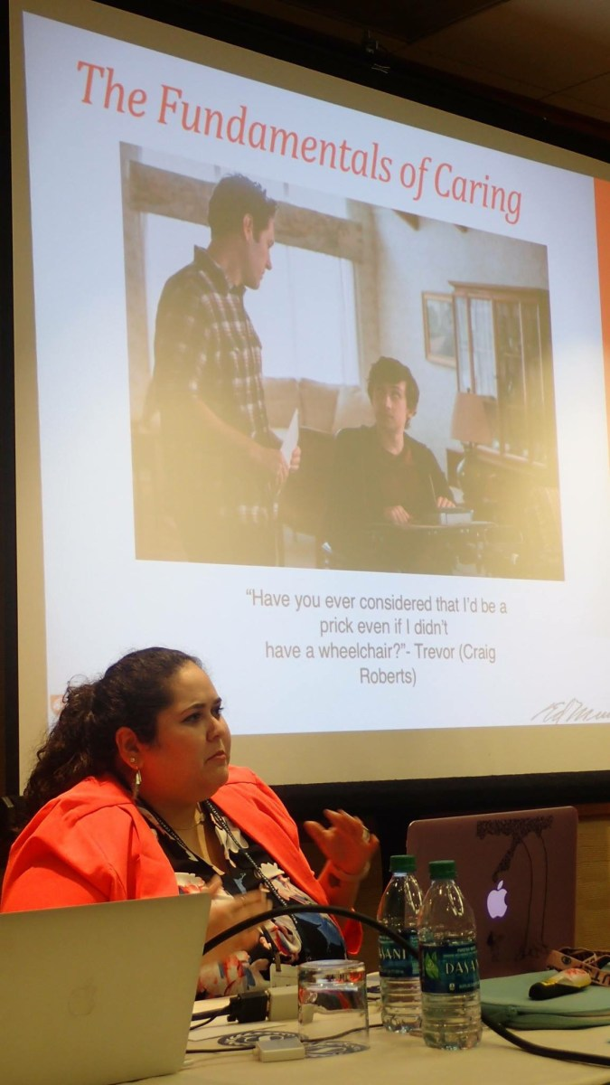 Photo of Davi presenting to an audience with a powerpoint screen behind her.