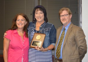 Image of A+ Teacher Theresa Mosier (center) with Davinci President Steve Wilson and principal Shelley Jaques-McMillin on each side. Mosier is holding a plaque commemorating her award.