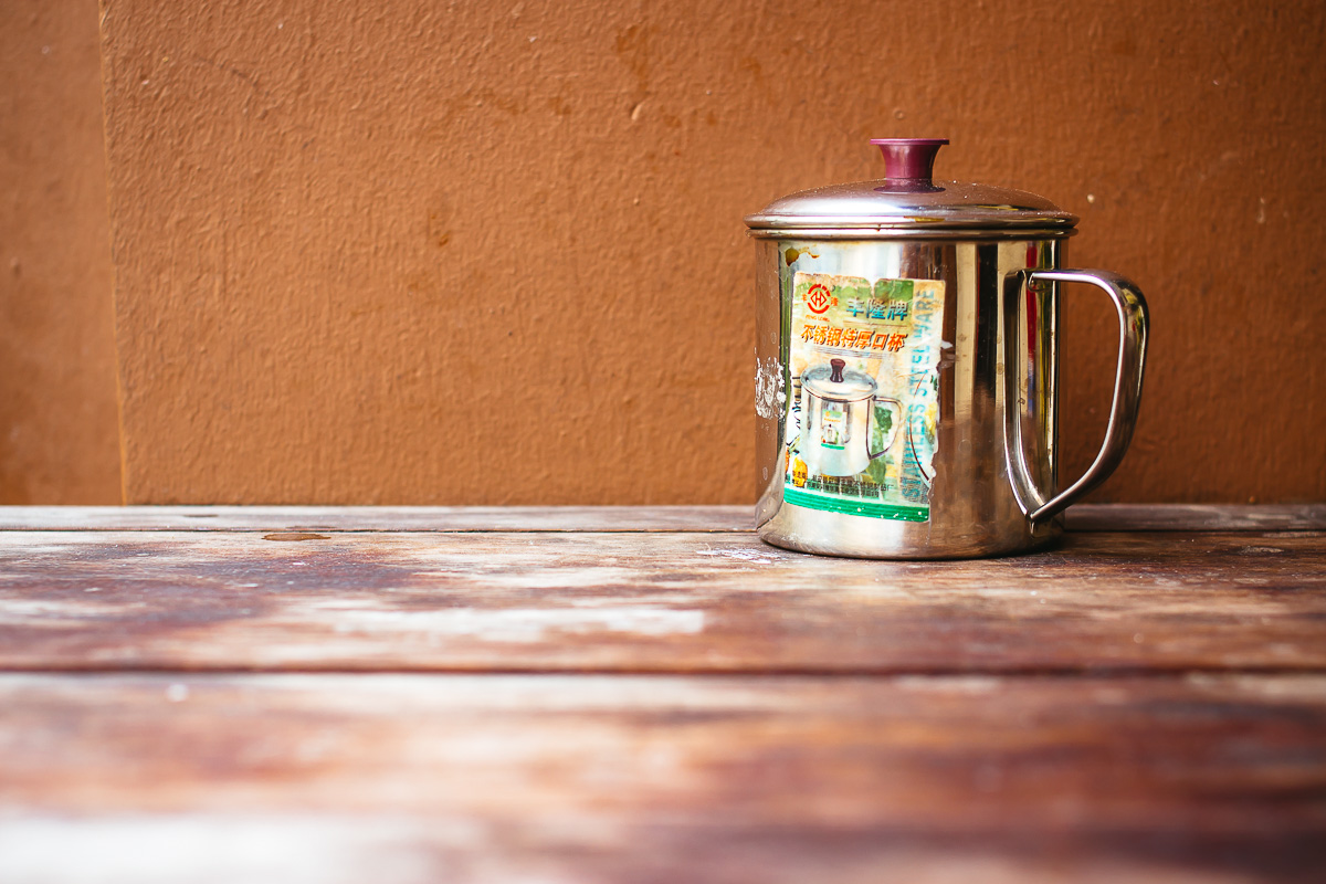 Metal tea can on wooden table in front of brown wall
