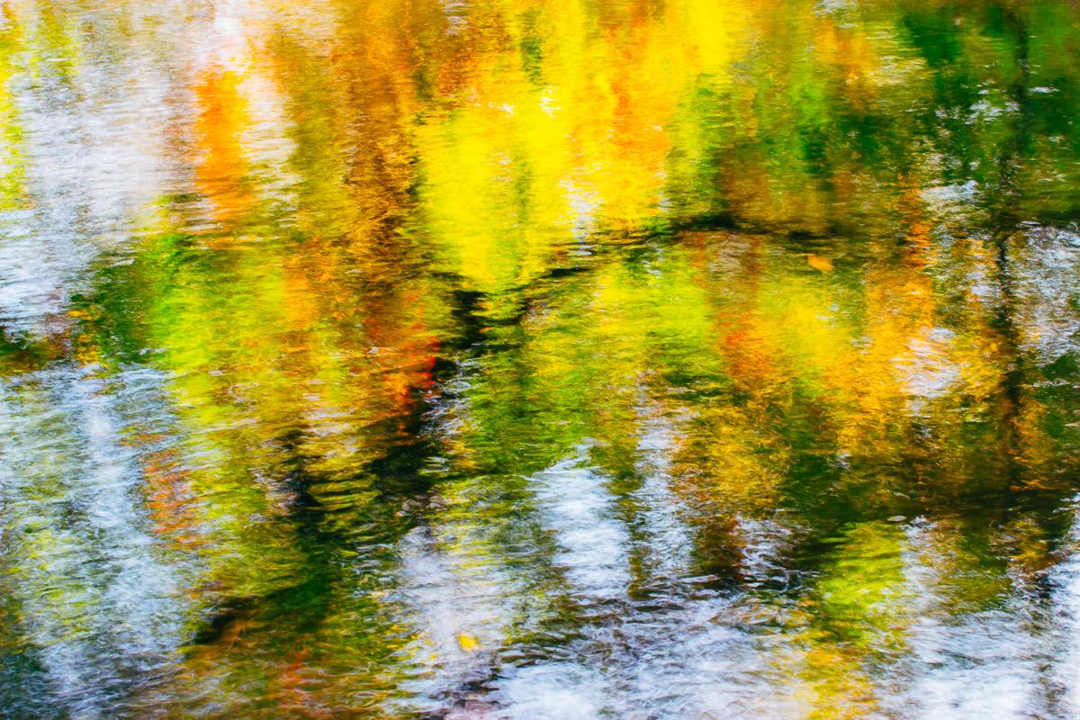Abstraktes Bild einer Wasseroberfläche mit bunten Spiegelungen in den Farben des Herbstlaubes.