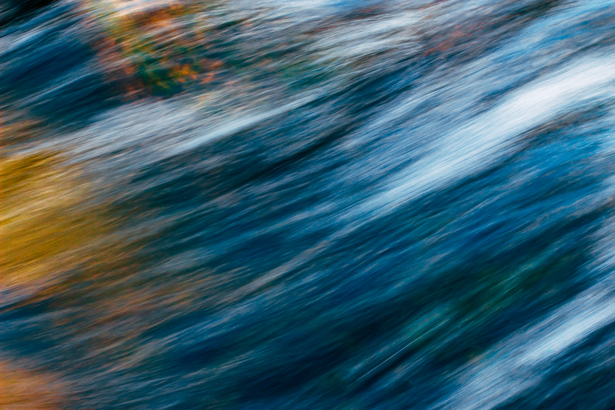 Abstract image of streaming water in dark blue with white streaks