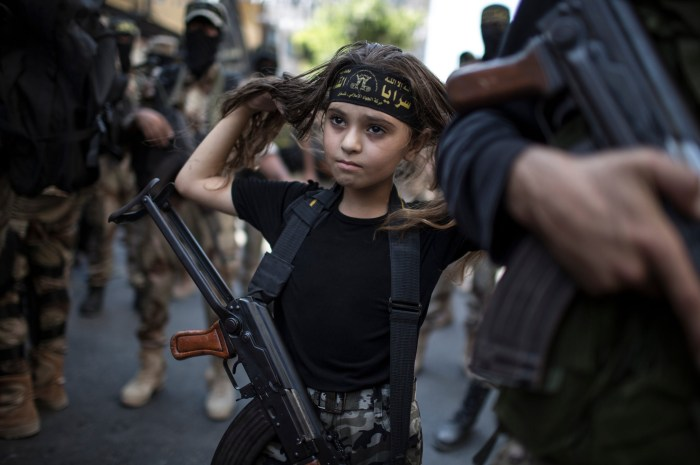 A Palestinian girl with a Kalashnikov rifle, amid Islamic Jihad militants in Gaza City