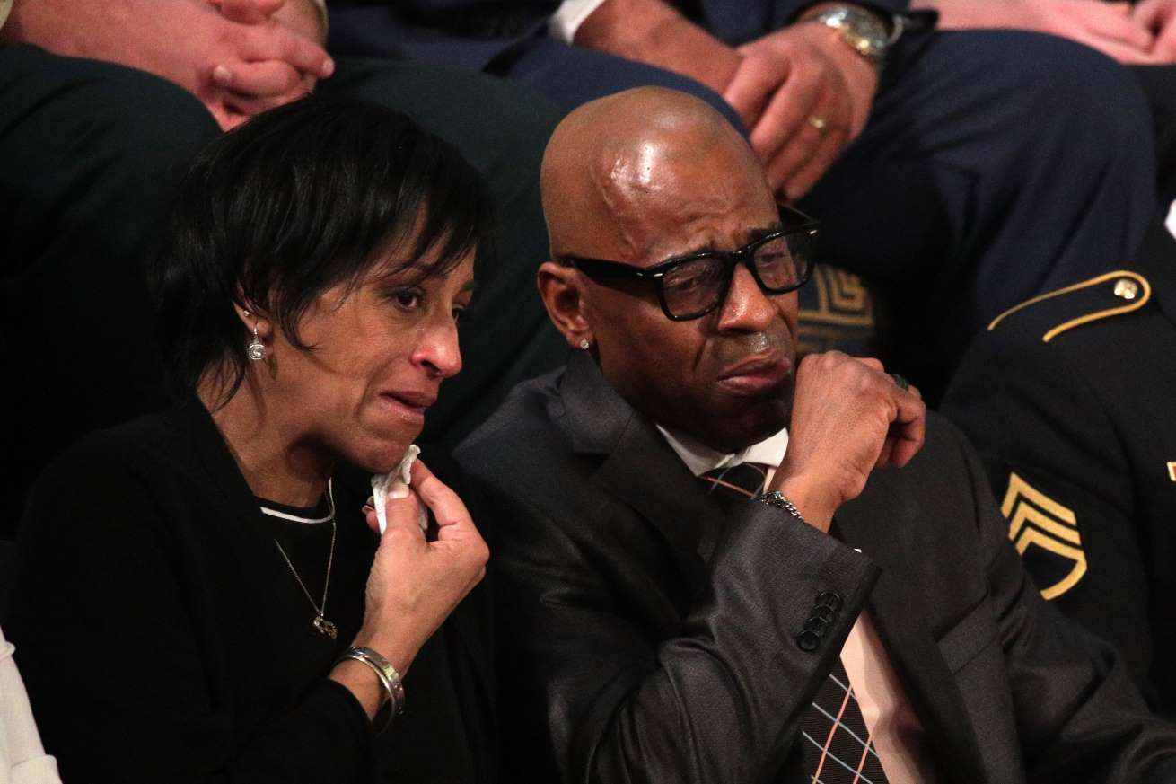a man talking on a cell phone: Evelyn Rodriguez and Freddy Cuevas, parents of a girl prosecutors say MS-13 killed, wipe away tears during President Trump's State of the Union speech.